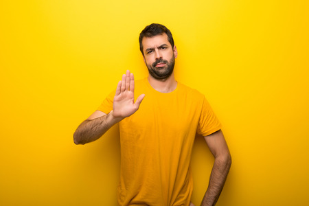 Man on isolated vibrant yellow color making stop gesture denying a situation that thinks wrong
