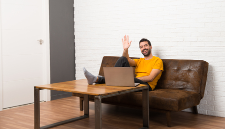 Man with his laptop in a room saluting with hand with happy expression