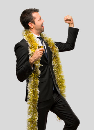 Man with champagne celebrating new year 2019 celebrating a victory and surprised to be successful on isolated grey background
