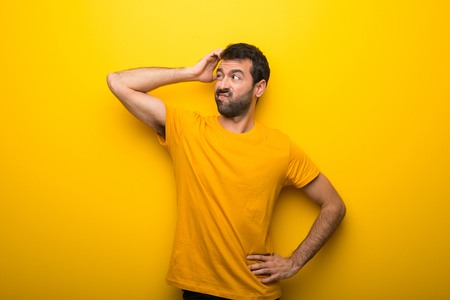 Man on isolated vibrant yellow color having doubts while scratching head Stock Photo