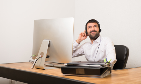 Telemarketer man in a office thinking an idea while scratching head