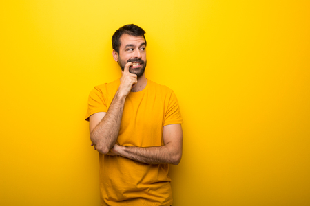 Man on isolated vibrant yellow color having doubts while looking up Stock Photo