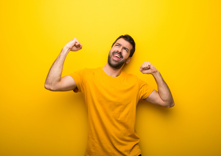 Man on isolated vibrant yellow color celebrating a victory in winner position