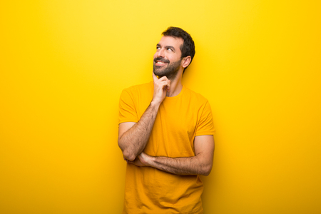 Man on isolated vibrant yellow color thinking an idea while looking up