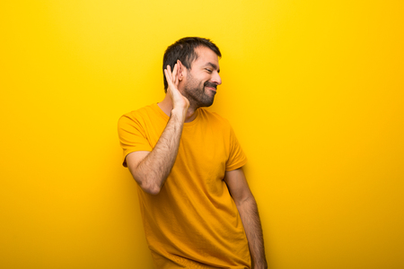 Man on isolated vibrant yellow color listening to something by putting hand on the ear