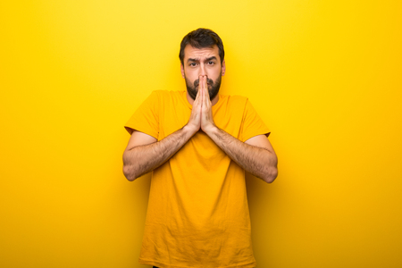 Man on isolated vibrant yellow color keeps palm together. Person asks for something