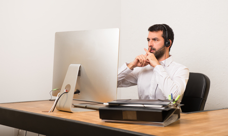 Telemarketer man in a office showing a sign of silence gesture Banco de Imagens