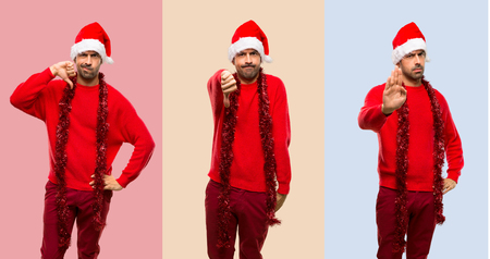 Set of Man with red clothes celebrating the Christmas holidays showing thumb down and stop getsure
