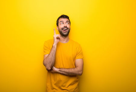 Man on isolated vibrant yellow color thinking an idea pointing the finger up Foto de archivo