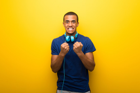 African american man with blue t-shirt on yellow background frustrated by a bad situation Stock Photo