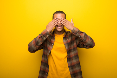 Young african american man on vibrant yellow background covering eyes by hands. Surprised to see what is ahead Stock Photo