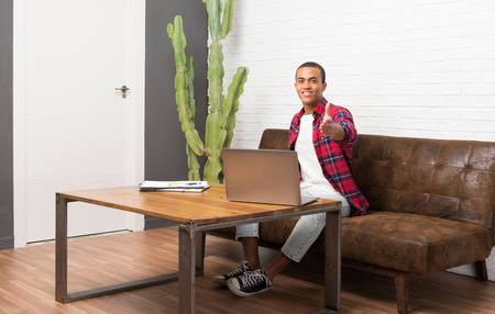 African american man with laptop in the living room shaking hands for closing a good deal Фото со стока