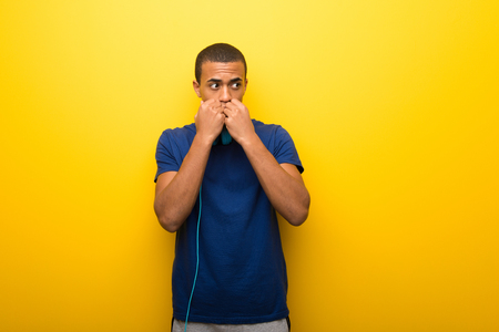 African american man with blue t-shirt on yellow background is a little bit nervous and scared putting hands to mouth Foto de archivo