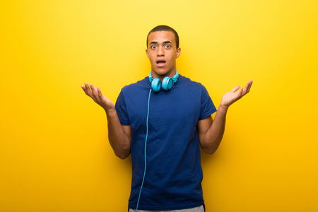 African american man with blue t-shirt on yellow background having doubts while raising hands and shoulders