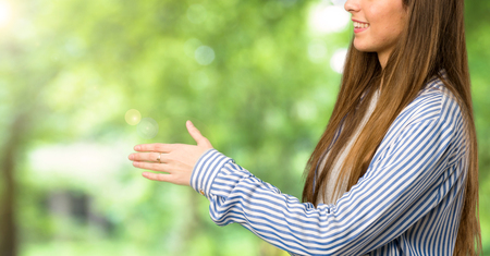 Young girl with striped shirt handshaking after good deal at outdoors
