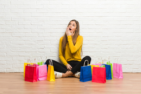 Young girl with lot of shopping bags yawning and covering wide open mouth with hand