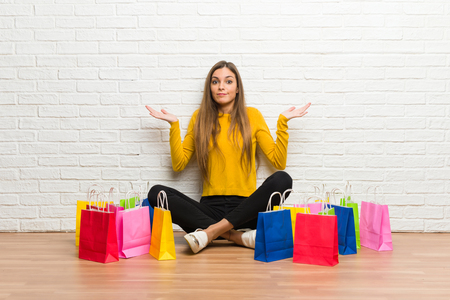 Young girl with lot of shopping bags having doubts while raising hands and shoulders