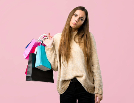 Young girl with shopping bags with sad and depressed expression on isolated pink background Фото со стока