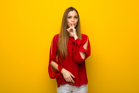 Young girl with red dress over yellow wall showing a sign of silence gesture putting finger in mouth Imagens - 113483668