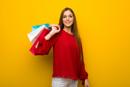 Young girl with red dress over yellow wall holding a lot of shopping bags Stock Photo