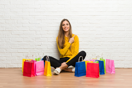 Young girl with lot of shopping bags pointing to the side to present a product