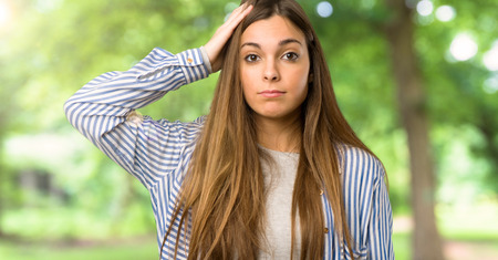 Young girl with striped shirt with an expression of frustration and not understanding at outdoors