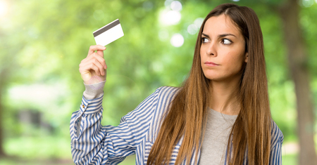 Young girl with striped shirt taking a credit card without money at outdoors