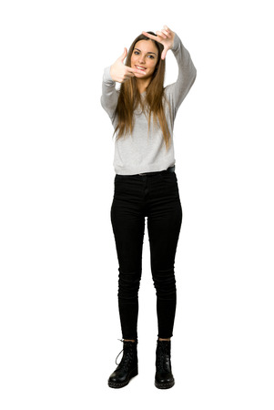 Full-length shot of young girl focusing face. Framing symbol on isolated white background