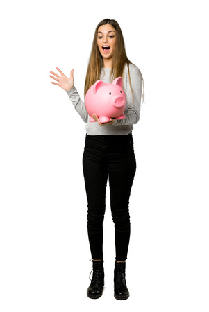 Full-length shot of young girl surprised while holding a piggybank on isolated white background