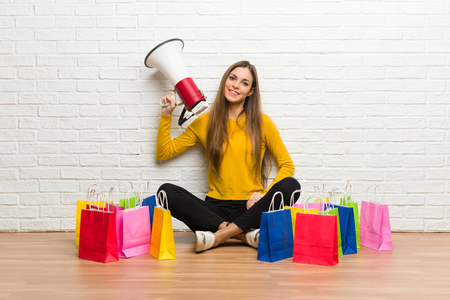 Young girl with lot of shopping bags holding a megaphone