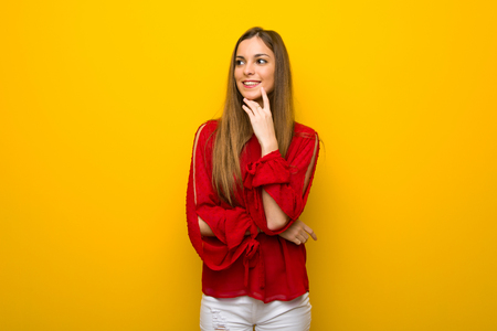 Young girl with red dress over yellow wall smiling with a sweet expression