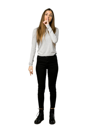 Full-length shot of young girl showing a sign of silence gesture putting finger in mouth on isolated white background Stock Photo