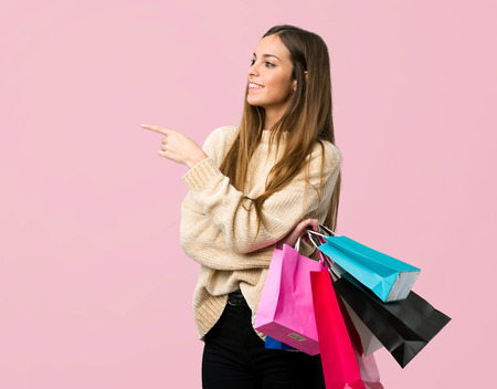 Young girl with shopping bags pointing finger to the side in lateral position on isolated pink background