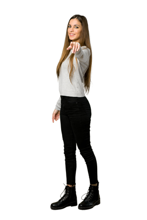 Full-length shot of young girl points finger at you with a confident expression on isolated white background Stock Photo