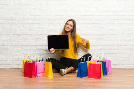 Young girl with lot of shopping bags showing a laptop