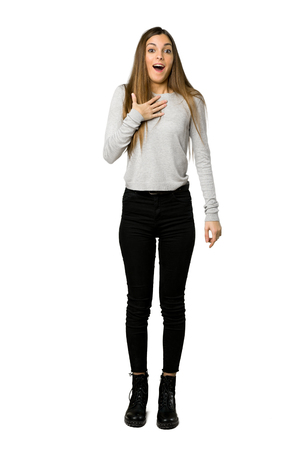 Full-length shot of young girl surprised and shocked while looking right on isolated white background Stock Photo