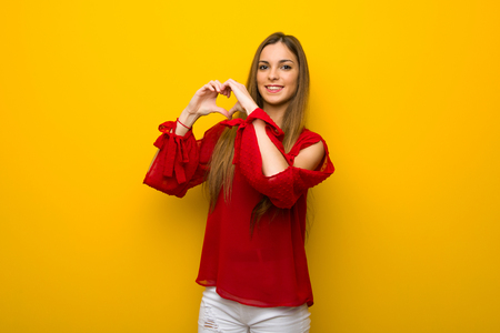 Young girl with red dress over yellow wall making heart symbol by hands