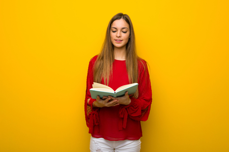 Young girl with red dress over yellow wall holding a book and enjoying reading Stock Photo