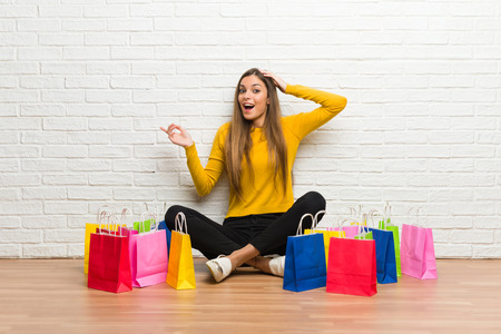 Young girl with lot of shopping bags pointing finger to the side and presenting a product Stock Photo
