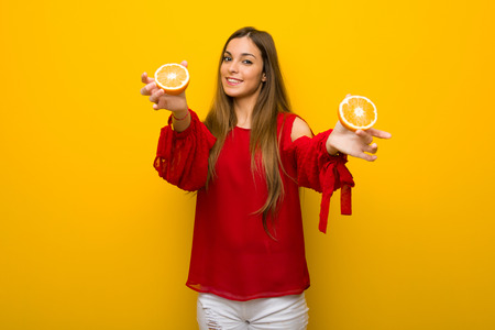 Young girl  on vibrant yellow background with oranges Stock Photo
