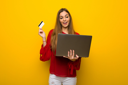 Young girl with red dress over yellow wall with laptop and credit card