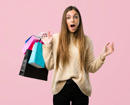 Young girl with shopping bags with surprise and shocked facial expression on isolated pink background