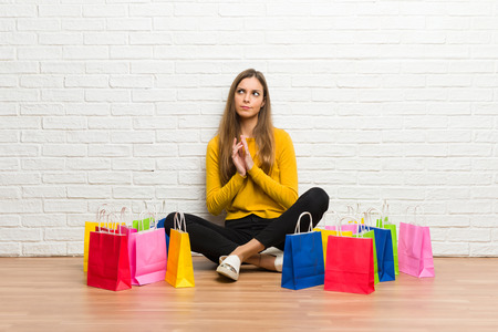 Young girl with lot of shopping bags scheming something