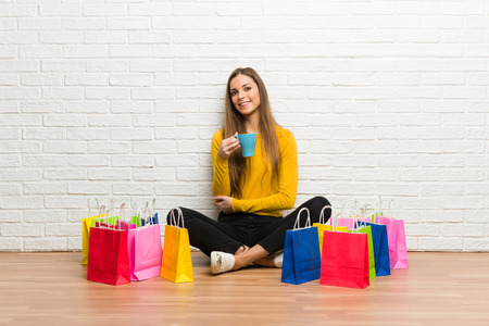 Young girl with lot of shopping bags holding a hot cup of coffee
