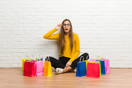 Young girl with lot of shopping bags with glasses and surprised Stock Photo