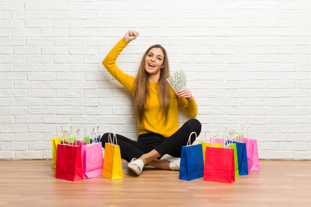 Young girl with lot of shopping bags taking a lot of money