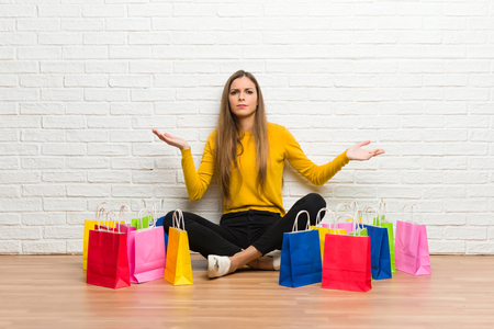 Young girl with lot of shopping bags unhappy and frustrated with something because not understand something