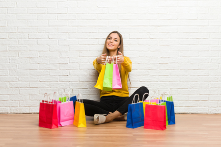 Young girl with lot of shopping bags holding a lot of shopping bags