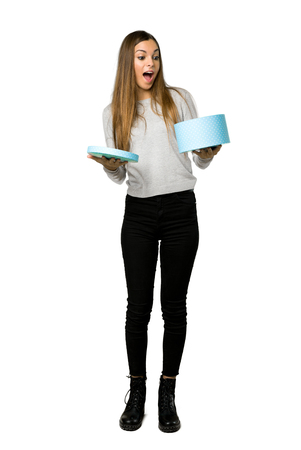 Full-length shot of young girl holding gift box in hands on isolated white background