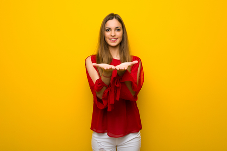 Young girl with red dress over yellow wall holding copyspace imaginary on the palm to insert an ad
